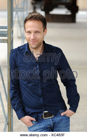 Smiling man leaning against wall - Stock Photo