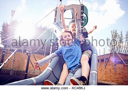 Boys coming down slide - Stock Photo