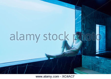 Woman sitting on window ledge and looking at underwater view of swimming pool - Stock Photo