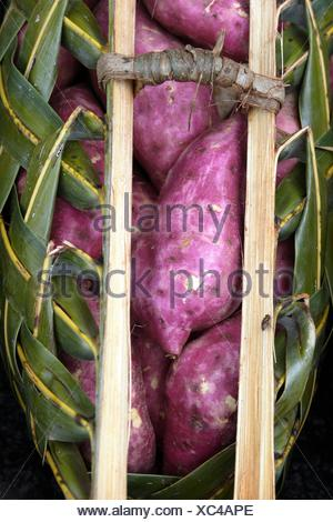 Purple colored sweet potatoes in a basket made of palm leaves on a market, Port Vila, Islands of Vanuatu, Melanesia, South - Stock Photo