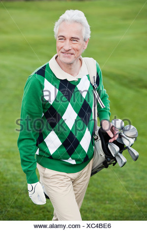 Italy, Kastelruth, Mature man walking on golf course, smiling - Stock Photo