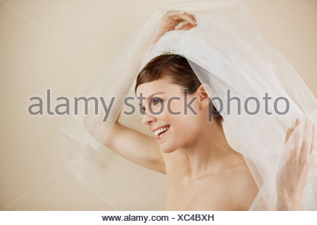 A young bride lifting her veil, smiling - Stock Photo