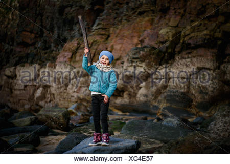 Girl standing on rock at the beach holding a stick - Stock Photo
