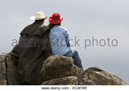 Female and male in western attire sitting together on the rocks out in the country looking off into the distance beyond them. - Stock Photo