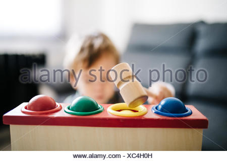Little boy playing with wooden motor skill toy, close-up - Stock Photo