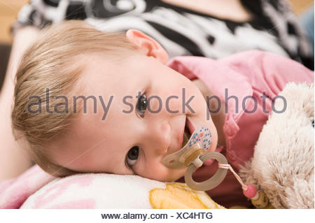 Tired baby girl 18 months old in bed with dummy - Stock Photo