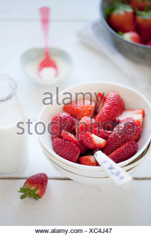 Fresh strawberry slices in bowl with milk bottle on table - Stock Photo