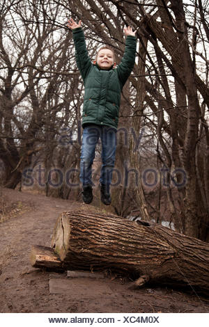Boy jumping off tree trunk in forest, Sofia, Bulgaria - Stock Photo