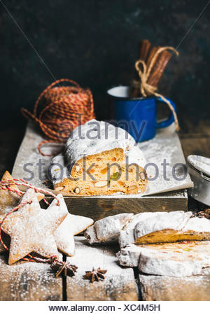 Traditional German Christmas cake Stollen with festive gingerbread cookies, selective focus, dark blue grunge background, copy space - Stock Photo