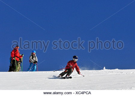 A young male skier skiing in the backcountry while his instructor looks on at Kirkwood Mountain Resort, CA. - Stock Photo