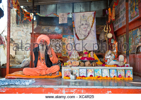 Sadhu, a holy man or wandering ascetic sitting in the lotus position on a mat in a Hindu prayer shrine, Pushkar, Rajasthan - Stock Photo
