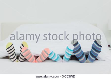 Familys feet in stripey socks - Stock Photo