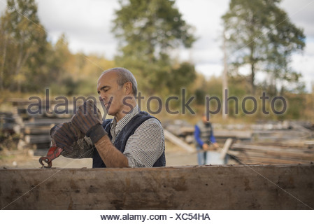 Two men working in a reclaimed timber yard One using a tool to remove metals from a reclaimed piece of timber - Stock Photo