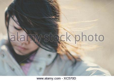 Girl (8-9) portrait on windy day - Stock Photo