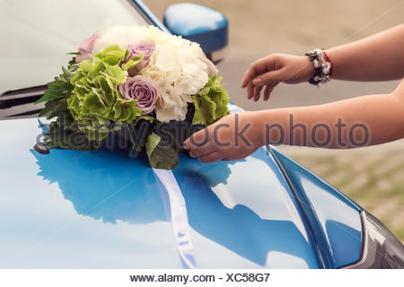 Wedding bouquet on a car bonnet - Stock Photo