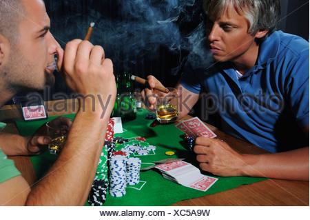 Two men playing poker, studio shot - Stock Photo