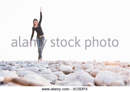 Young woman walking barefoot on stones at coast - Stock Photo