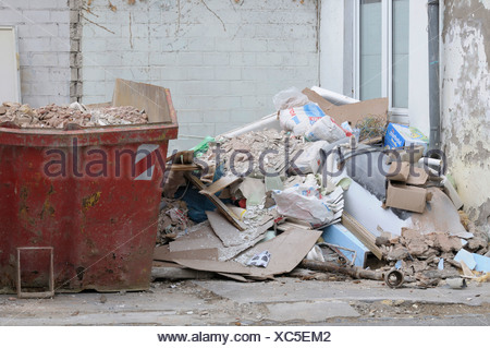 Tenement reconstruction, filled red skip, pile of debris on the side, new window at back - Stock Photo