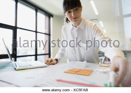 Focused architect arranging models in office - Stock Photo