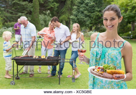 Portrait of smiling woman holding plate of barbecue and glass of wine with family in background - Stock Photo