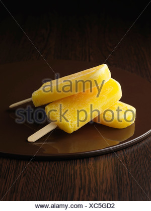 Lemon popsicles on wooden plate - Stock Photo