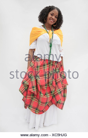 Portrait of smiling young woman wearing a traditional dress from the Caribbean, studio shot - Stock Photo