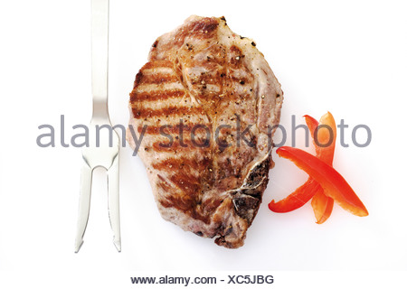 Grilled Pork chop and meat fork, elevated view - Stock Photo