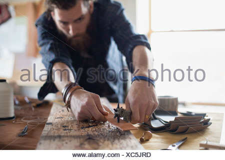 Man punching holes in leather belt at table - Stock Photo