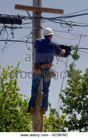 Electrician working up high on a utility pole - Stock Photo