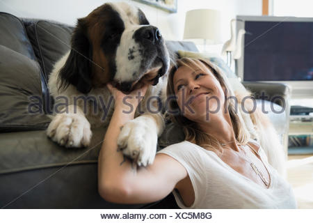 Woman petting Saint Bernard dog on sofa - Stock Photo