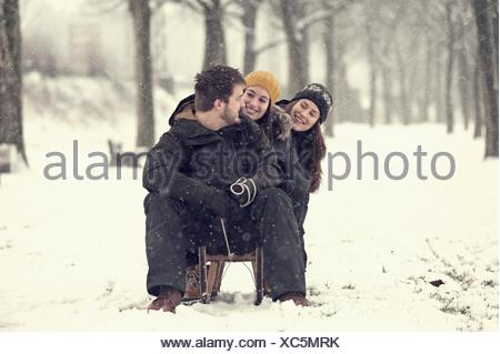 Three friends sitting on sledge in winter - Stock Photo