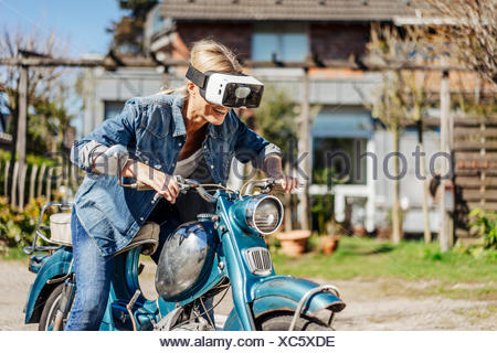 Happy woman on vintage motorcycle wearing VR glasses - Stock Photo