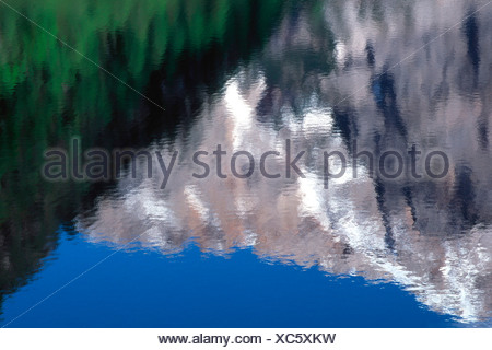 Reflection of green forests and snow capped mountains under blue sky in the Pragser Wildsee lake or Lago di Braies, Bolzano-Boz - Stock Photo