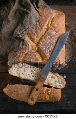 Fresh slice artisan bread under sackcloth with vintage knife over old wooden background. Overhead view. - Stock Photo