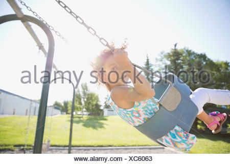 Portrait of little girl swinging at park - Stock Photo