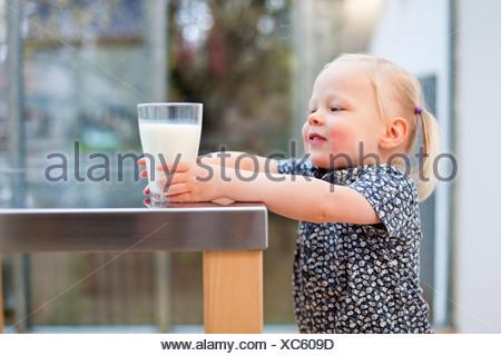 Toddler girl holding glass of milk - Stock Photo