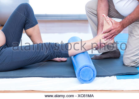 Low section of instructor teaching exercise to pregnant woman - Stock Photo