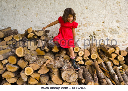 A girl climbing on logs - Stock Photo
