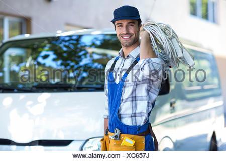 Portrait of happy carpenter with wire - Stock Photo