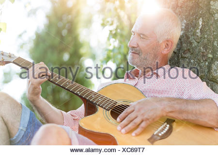 Senior man playing guitar against tree trunk - Stock Photo