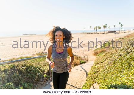 Mid adult woman running along pathway by beach - Stock Photo