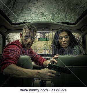 Man and woman in car with handgun - Stock Photo