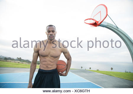 Portrait of a young man holding a basketball in a park, Los Angeles, California, USA - Stock Photo