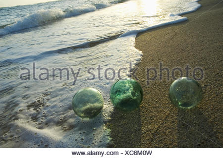 Three Glass Fishing Floats Roll On The Sandy Shoreline With Ripples Of Water And Seafoam - Stock Photo