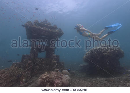 Woman snorkeling underwater by a sunken temple, Bali, Indonesia - Stock Photo