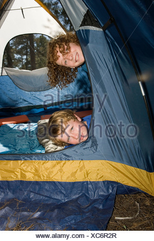 Two young boys peeking out of a tent - Stock Photo