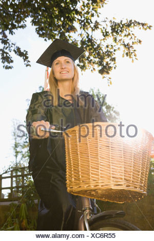 Female Student At Graduation Riding Bicycle - Stock Photo