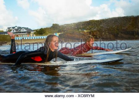 Two surfers paddling on surfboards - Stock Photo