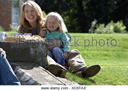 Mother and daughter 2 3 sitting on grass in garden having tea and sandwiches laughing - Stock Photo