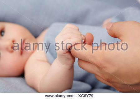 Baby boy holding mothers finger in bed - Stock Photo
